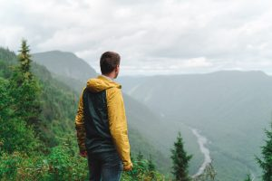 Ben on the peak of a mountain in Quebec, looking out into the vista with rivers in the valley