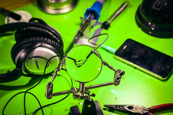 Bright lime-green background with a pair of QC15 headphones and iPhone 4 in the background and three wires soldered together, holding two severed side of the headphone cable together