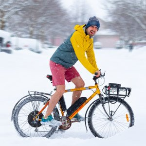 ben in red shorts on a yellow ebike in a snow storm with a bright yellow jacket on, laughing